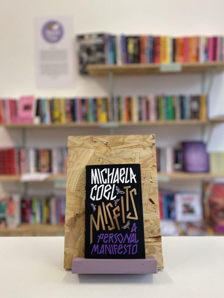 Cymraeg: Copi o 'Misfits' yn sefyll ar stondin llyfrau, tu blaen silffoedd o lyfrau yn y cefndir. English: A copy of 'Misfits' sits on a stand in front of multiple shelves of other books.