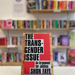 Cymraeg: Copi o 'The Transgender Issue' yn sefyll ar stondin llyfrau, tu blaen silffoedd o lyfrau yn y cefndir. English: A copy of 'The Transgender Issue' sits on a stand in front of multiple shelves of other books.