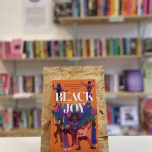 Cymraeg: Copi o 'Black Joy' yn sefyll ar stondin llyfrau, tu blaen silffoedd o lyfrau yn y cefndir. English: A copy of 'Black Joy' sits on a stand in front of multiple shelves of other books.
