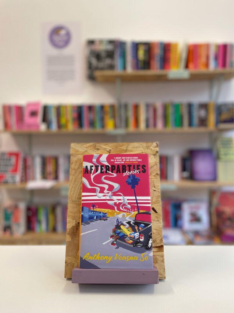 Cymraeg: Copi o 'Afterparties' yn sefyll ar stondin llyfrau, tu blaen silffoedd o lyfrau yn y cefndir. English: A copy of 'Afterparties' sits on a stand in front of multiple shelves of other books.