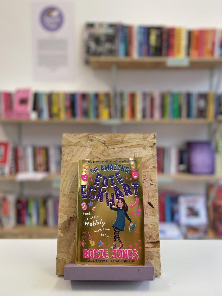 Cymraeg: Copi o 'The Amazing Edie Eckhart' yn sefyll ar stondin llyfrau, tu blaen silffoedd o lyfrau yn y cefndir. English: A copy of 'The Amazing Edie Eckhart' sits on a stand in front of multiple shelves of other books.