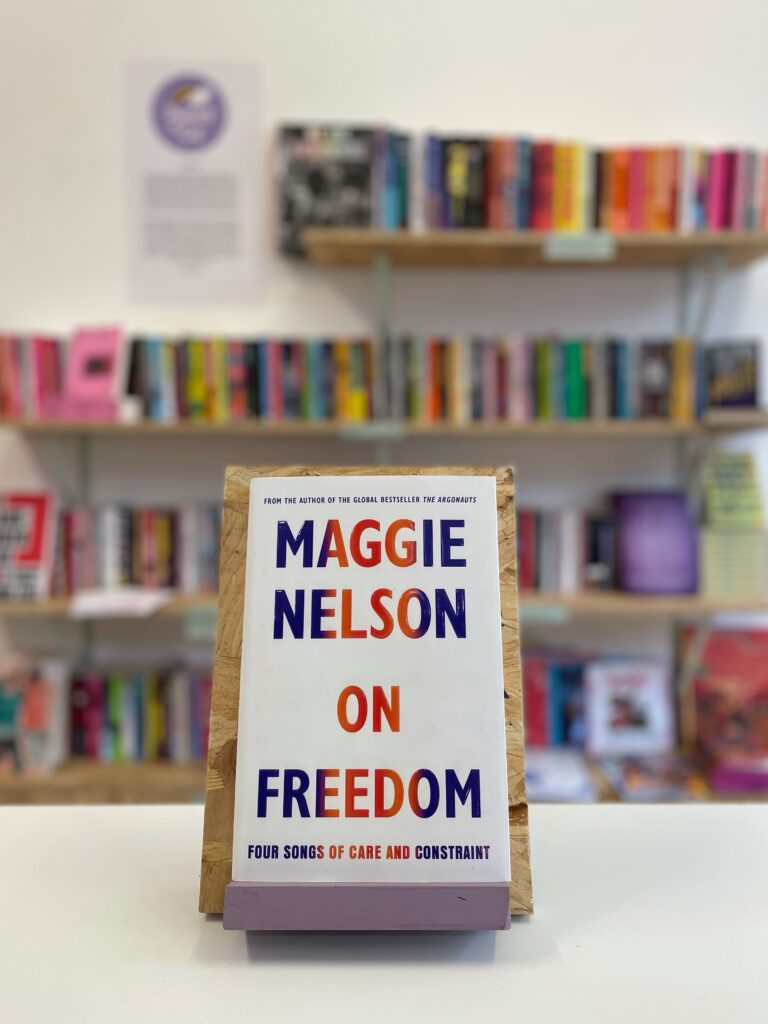 Cymraeg: Copi o 'On Nelson' yn sefyll ar stondin llyfrau, tu blaen silffoedd o lyfrau yn y cefndir. English: A copy of 'On Freedom' sits on a stand in front of multiple shelves of other books.