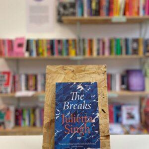 Cymraeg: Copi o 'The Breaks' yn sefyll ar stondin llyfrau, tu blaen silffoedd o lyfrau yn y cefndir. English: A copy of 'The Breaks' sits on a stand in front of multiple shelves of other books.