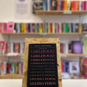 Cymraeg: Copi o 'Girlhood' yn sefyll ar stondin llyfrau, tu blaen silffoedd o lyfrau yn y cefndir. English: A copy of 'Girlhood' sits on a stand in front of multiple shelves of other books.