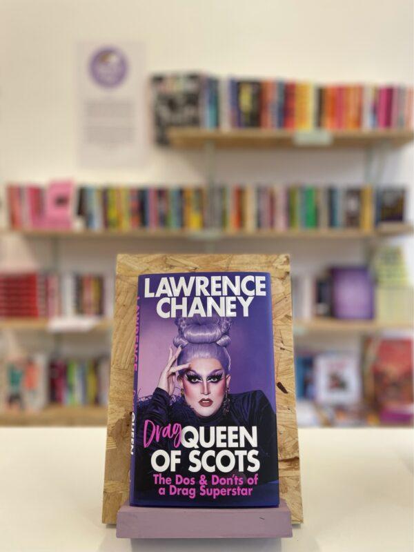 Cymraeg: Copi o 'Drag Queen of Scots' yn sefyll ar stondin llyfrau, tu blaen silffoedd o lyfrau yn y cefndir. | English: A copy of 'Drag Queen of Scots' sits on a stand in front of multiple shelves of other books.