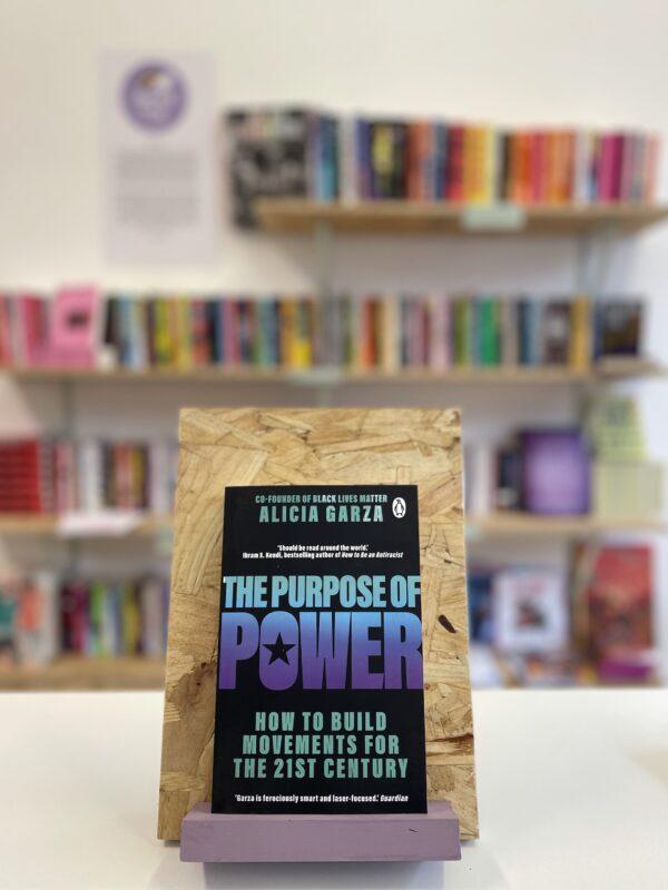 Cymraeg: Copi o 'The Purpose of Power' yn sefyll ar stondin llyfrau, tu blaen silffoedd o lyfrau yn y cefndir. | English: A copy of 'The Purpose of Power' sits on a stand in front of multiple shelves of other books.
