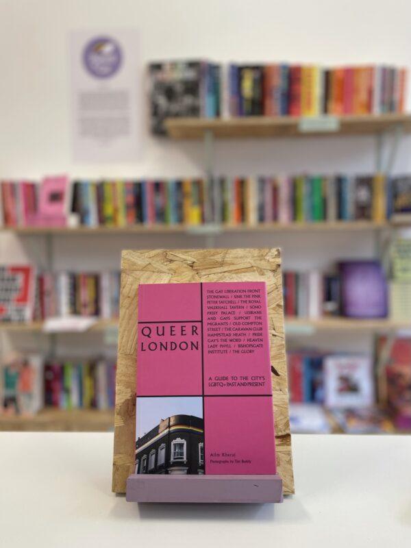 Cymraeg: Copi o 'Queer London' yn sefyll ar stondin llyfrau, tu blaen silffoedd o lyfrau yn y cefndir. | English: A copy of 'Queer London' sits on a stand in front of multiple shelves of other books.