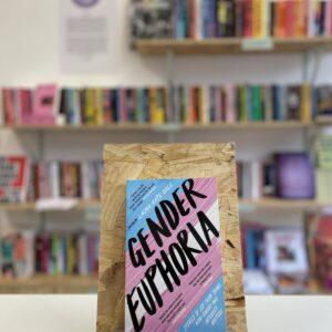 Cymraeg: Copi o 'Gender Euphoria' yn sefyll ar stondin llyfrau, tu blaen silffoedd o lyfrau yn y cefndir. | English: A copy of 'Gender Euphoria' sits on a stand in front of multiple shelves of other books.