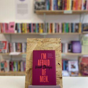 Cymraeg: Copi o 'I'm Afraid of Men' yn sefyll ar stondin llyfrau, tu blaen silffoedd o lyfrau yn y cefndir. | English: A copy of 'I'm Afraid of Men' sits on a stand in front of multiple shelves of other books.