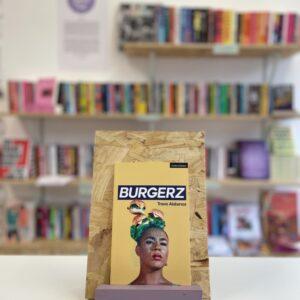 Cymraeg: Copi o 'Burgerz' yn sefyll ar stondin llyfrau, tu blaen silffoedd o lyfrau yn y cefndir. English: A copy of 'Burgerz' sitson a stand in front of multiple shelves of other books.