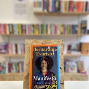 Cymraeg: Copi o 'Manifesto' yn sefyll ar stondin llyfrau, tu blaen silffoedd o lyfrau yn y cefndir. | English: A copy of 'Manifesto' sits on a stand in front of multiple shelves of other books.