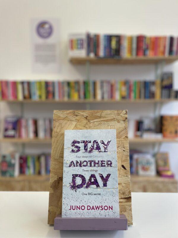 Cymraeg: Copi o 'Stay Another Day' yn sefyll ar stondin llyfrau, tu blaen silffoedd o lyfrau yn y cefndir. | English: A copy of 'Stay Another Day' sits on a stand in front of multiple shelves of other books.
