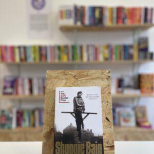 Cymraeg: Copi o 'Shuggie Bain' yn sefyll ar stondin llyfrau, tu blaen silffoedd o lyfrau yn y cefndir. | English: A copy of 'Shuggie Bain' sits on a stand in front of multiple shelves of other books.
