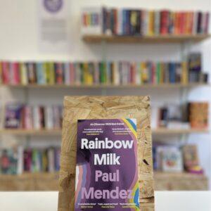 Cymraeg: Copi o 'Rainbow Milk' yn sefyll ar stondin llyfrau, tu blaen silffoedd o lyfrau yn y cefndir. | English: A copy of 'Rainbow Milk' sits on a stand in front of multiple shelves of other books.
