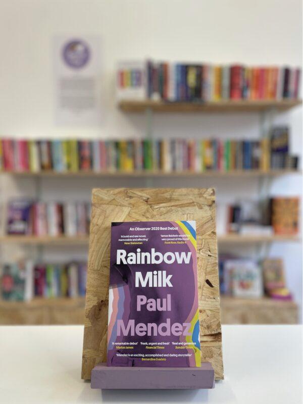 Cymraeg: Copi o 'Rainbow Milk' yn sefyll ar stondin llyfrau, tu blaen silffoedd o lyfrau yn y cefndir.   English: A copy of 'Rainbow Milk' sits on a stand in front of multiple shelves of other books.
