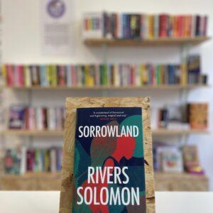 Cymraeg: Copi o 'Sorrowland' yn sefyll ar stondin llyfrau, tu blaen silffoedd o lyfrau yn y cefndir. | English: A copy of 'Sorrowland' sits on a stand in front of multiple shelves of other books.