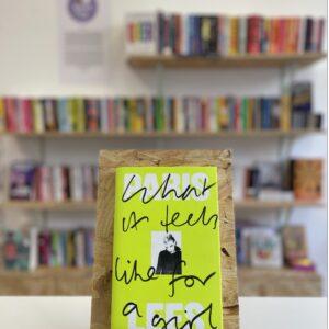 Cymraeg: Copi o 'What It Feels Like to Be a Girl' yn sefyll ar stondin llyfrau, tu blaen silffoedd o lyfrau yn y cefndir. | English: A copy of 'What It Feels Like For a Girl' sits on a stand in front of multiple shelves of other books.
