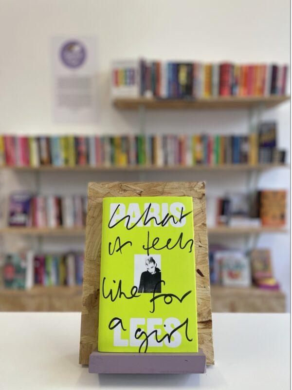 Cymraeg: Copi o 'What It Feels Like to Be a Girl' yn sefyll ar stondin llyfrau, tu blaen silffoedd o lyfrau yn y cefndir.   English: A copy of 'What It Feels Like For a Girl' sits on a stand in front of multiple shelves of other books.