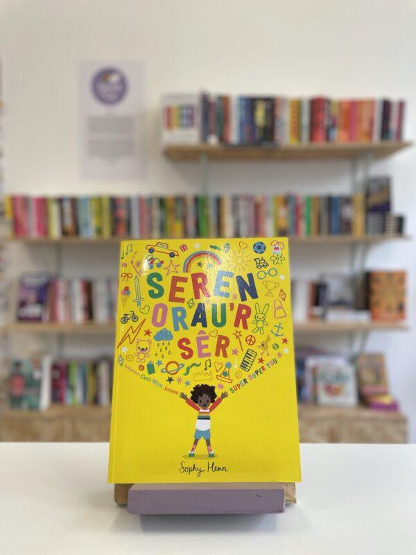 Cymraeg: Copi o 'Seren Orau'r Sêr' yn sefyll ar stondin llyfrau, tu blaen silffoedd o lyfrau yn y cefndir.   English: A copy of 'Seren Orau'r Sêr' sits on a stand in front of multiple shelves of other books.