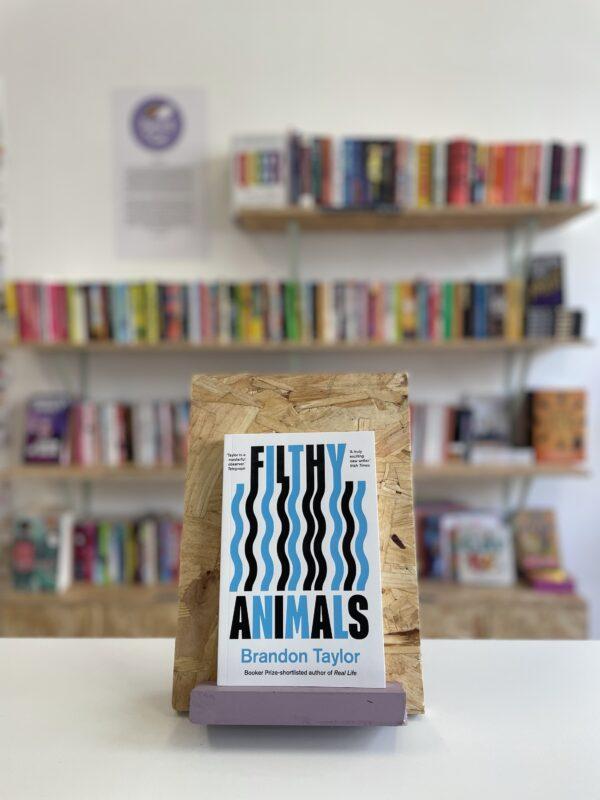 Cymraeg: Copi o 'Filthy Animals' yn sefyll ar stondin llyfrau, tu blaen silffoedd o lyfrau yn y cefndir. | English: A copy of 'Filthy Animals' sits on a stand in front of multiple shelves of other books.