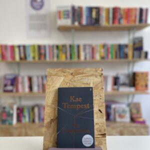 Cymraeg: Copi o 'On Connection' yn sefyll ar stondin llyfrau, tu blaen silffoedd o lyfrau yn y cefndir. | English: A copy of 'On Connection' sits on a stand in front of multiple shelves of other books.