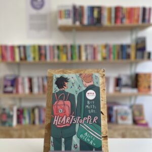 Cymraeg: Copi o 'Heartstopper vol. 1' yn sefyll ar stondin llyfrau, tu blaen silffoedd o lyfrau yn y cefndir. | English: A copy of 'Heartstopper vol. 1' sits on a stand in front of multiple shelves of other books.