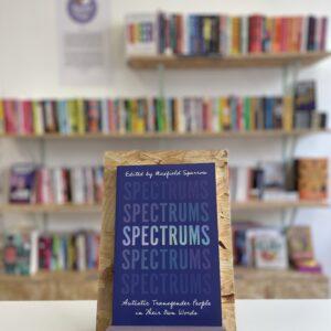 Cymraeg: Copi o 'Spectrums' yn sefyll ar stondin llyfrau, tu blaen silffoedd o lyfrau yn y cefndir. | English: A copy of 'Spectrums' sits on a stand in front of multiple shelves of other books.