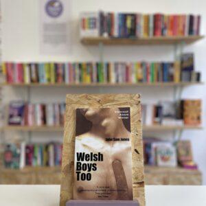 Cymraeg: Copi o 'Welsh Boys Too' yn sefyll ar stondin llyfrau, tu blaen silffoedd o lyfrau yn y cefndir. | English: A copy of 'Welsh Boys Too' sits on a stand in front of multiple shelves of other books.