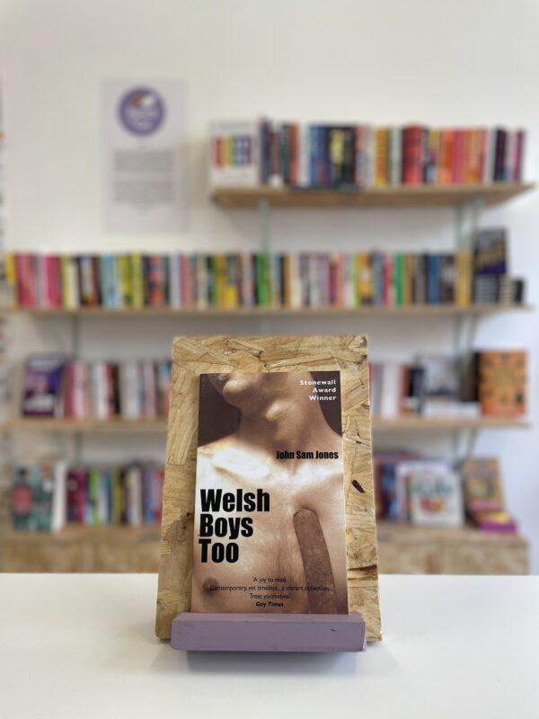 Cymraeg: Copi o 'Welsh Boys Too' yn sefyll ar stondin llyfrau, tu blaen silffoedd o lyfrau yn y cefndir.   English: A copy of 'Welsh Boys Too' sits on a stand in front of multiple shelves of other books.
