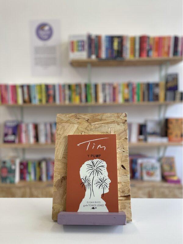 Cymraeg: Copi o 'Y Pump: Tim' yn sefyll ar stondin llyfrau, tu blaen silffoedd o lyfrau yn y cefndir. | English: A copy of 'Y Pump: Tim' sits on a stand in front of multiple shelves of other books.