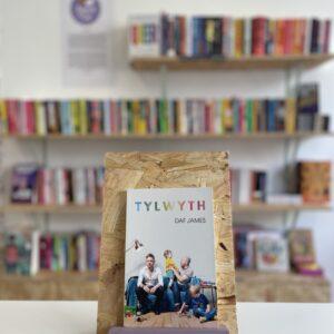 Cymraeg: Copi o 'Tylwyth' yn sefyll ar stondin llyfrau, tu blaen silffoedd o lyfrau yn y cefndir. | English: A copy of 'Tylwyth' sits on a stand in front of multiple shelves of other books.