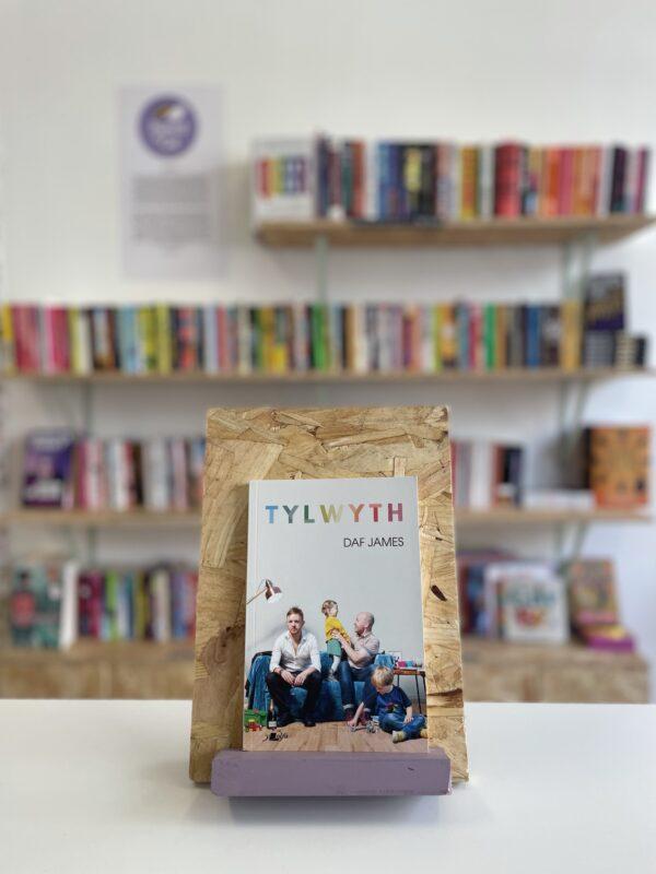 Cymraeg: Copi o 'Tylwyth' yn sefyll ar stondin llyfrau, tu blaen silffoedd o lyfrau yn y cefndir.   English: A copy of 'Tylwyth' sits on a stand in front of multiple shelves of other books.
