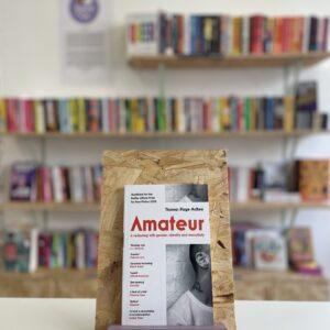 Cymraeg: Copi o 'Amateur' yn sefyll ar stondin llyfrau, tu blaen silffoedd o lyfrau yn y cefndir. | English: A copy of 'Amateur' sits on a stand in front of multiple shelves of other books.