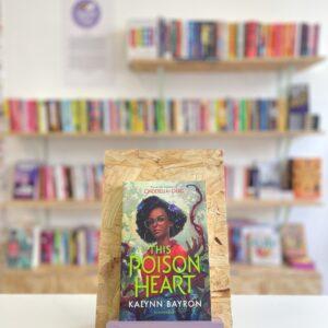 Cymraeg: Copi o 'The Poison Heart' yn sefyll ar stondin llyfrau, tu blaen silffoedd o lyfrau yn y cefndir. | English: A copy of 'The Poison Heart' sits on a stand in front of multiple shelves of other books.