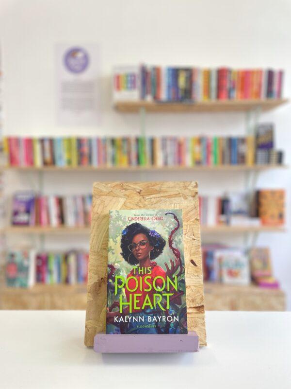Cymraeg: Copi o 'The Poison Heart' yn sefyll ar stondin llyfrau, tu blaen silffoedd o lyfrau yn y cefndir.   English: A copy of 'The Poison Heart' sits on a stand in front of multiple shelves of other books.