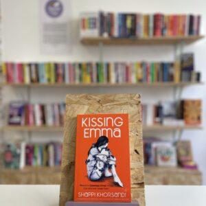 Cymraeg: Copi o 'Kissing Emma' yn sefyll ar stondin llyfrau, tu blaen silffoedd o lyfrau yn y cefndir. | English: A copy of 'Kissing Emma' sits on a stand in front of multiple shelves of other books.