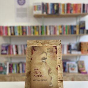 Cymraeg: Copi o 'The Gilda Stories' yn sefyll ar stondin llyfrau, tu blaen silffoedd o lyfrau yn y cefndir. | English: A copy of 'The Gilda Stories' sits on a stand in front of multiple shelves of other books.
