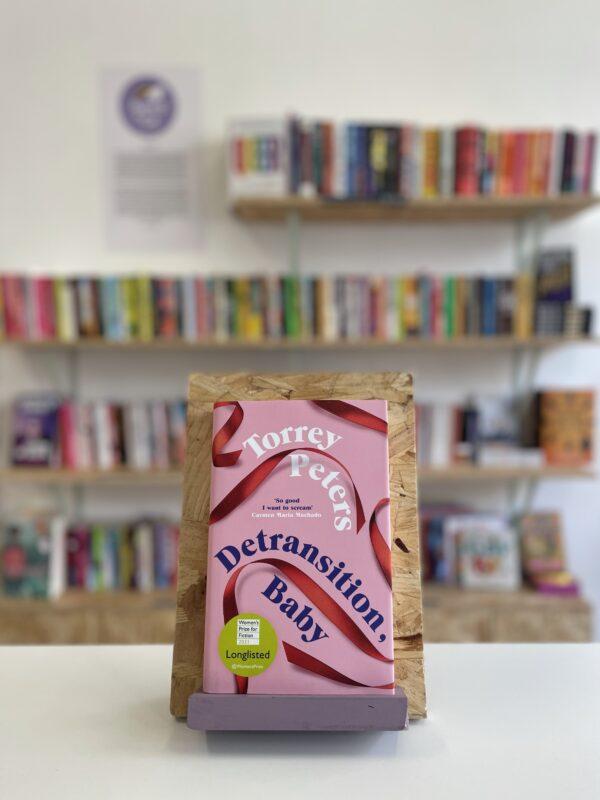 Cymraeg: Copi o 'Detransition, Baby' yn sefyll ar stondin llyfrau, tu blaen silffoedd o lyfrau yn y cefndir. | English: A copy of 'Detransition, Baby' sits on a stand in front of multiple shelves of other books.