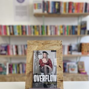Cymraeg: Copi o 'Overflow' yn sefyll ar stondin llyfrau, tu blaen silffoedd o lyfrau yn y cefndir. English: A copy of 'Overflow' sitson a stand in front of multiple shelves of other books.
