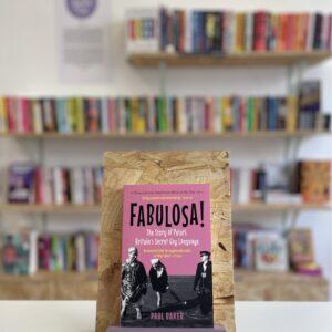 Cymraeg: Copi o 'Fabulosa' yn sefyll ar stondin llyfrau, tu blaen silffoedd o lyfrau yn y cefndir. | English: A copy of 'Fabulosa' sits on a stand in front of multiple shelves of other books.